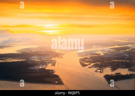Western Dvina Flows Into The Baltic Sea. River Divides The Northern And Kurzeme District Of Riga, Latvia. View From Airplane Flight. Sunset Sunrise - Stock Photo
