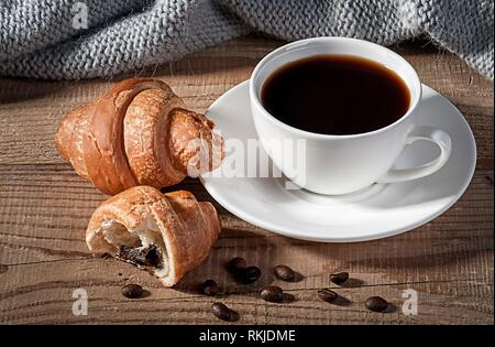 Black coffee with croissants. Coffee grains on a wooden table. Knitted woolen scarf in the background. - Stock Photo