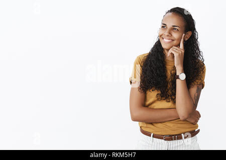 Indoor shot of happy carefree charming african-american delighted woman in t-shirt holding finger on temple smiling satisfied as gazing left nostalgic - Stock Photo