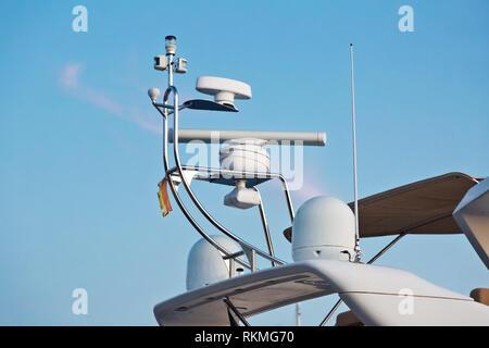 Closeup view of navigation radar system antennas yacht on blue sky background - Stock Photo