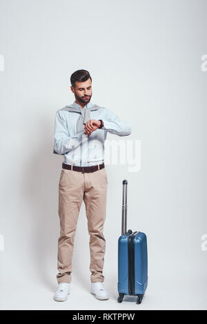 Time to go. Full length of young and stylish bearded man with a luggage checking time while standing on a grey background. Travel concept - Stock Photo
