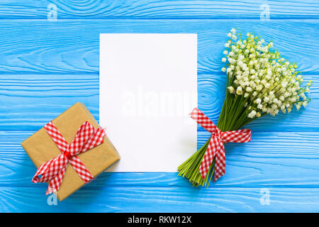 Mockup with bouquet of flowers lily of the valley and empty paper sheet on blue wooden table, gift box top view, - Stock Photo