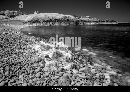 Infrared monochrome image of Crabby beach, Crabby Bay, near the Breakwater on Alderney, Channel Islands. - Stock Photo