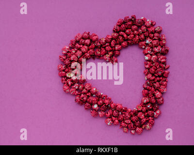 Red heart shape made from popcorn on a pink background - Stock Photo