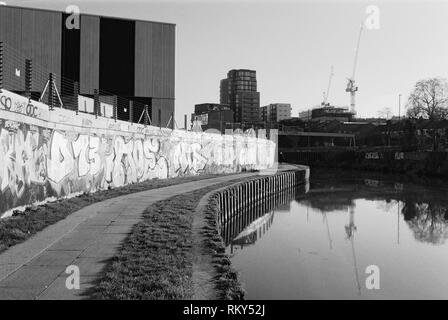 Wall with graffiti and footpath along the River Lea near Bromley-By-Bow, East London, UK, with modern buildings in background - Stock Photo