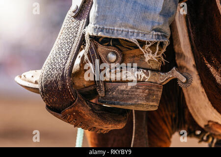 Close-up of cowboy boot with attached spur in a stirrup. - Stock Photo