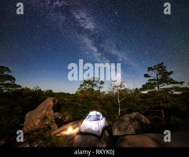 Camping at summer night on rocky mountain. Illuminated tourist tent and bonfire under amazing night sky full of stars and Milky way. On the background beautiful starry sky, big boulders and trees - Stock Photo