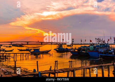 Fishing boats at sunset in the village of Tra Nhieu on the Thu Bon River near Hoi An, Vietnam. - Stock Photo
