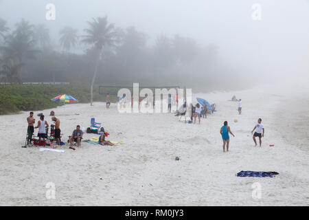 Tourists enjoying beach activities even though unusual afternoon fog has set in. - Stock Photo