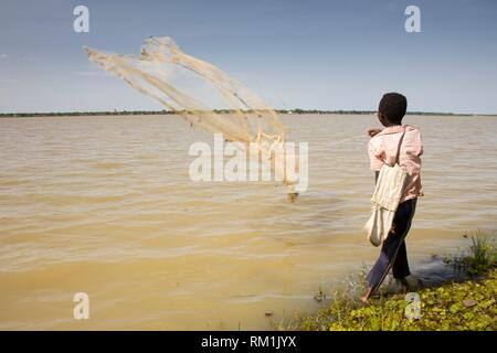 Bozo boy casting fishing net into the Niger River in a fishermen´s village opposite to Segou City. Mali - Stock Photo