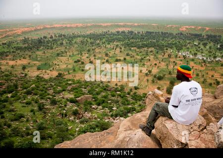 Mali, Dogon Country. Man looking at view, sitting on Bandiagara Escarpment. This escarpment, created by a geological fault, is 150 Km long and can - Stock Photo