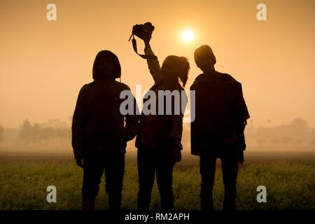 Silhouette of woman photographer and his friends at sunrise time. - Stock Photo