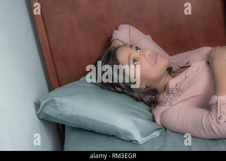 Young Hispanic woman lying on her bed. - Stock Photo