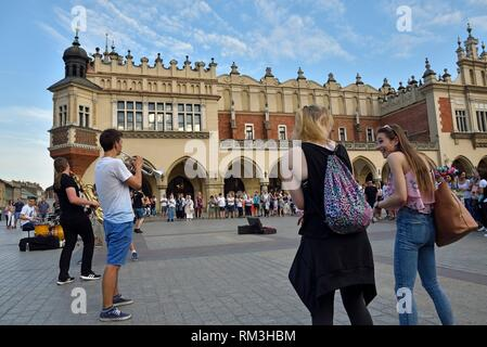 group of musicians in front of the Cloth Hall (Sukiennice) on Rynek Glowny, the main square of the Old Town of Krakow, Malopolska Province (Lesser - Stock Photo