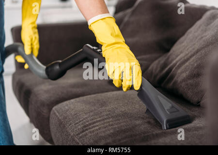 Cropped view of woman in rubber gloves cleaning sofa with vacuum cleaner - Stock Photo