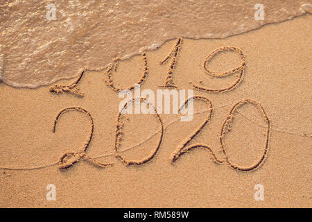 New Year 2020 is coming concept - inscription 2019 and 2020 a beach sand, the wave is almost covering the digits 2019 - Stock Photo