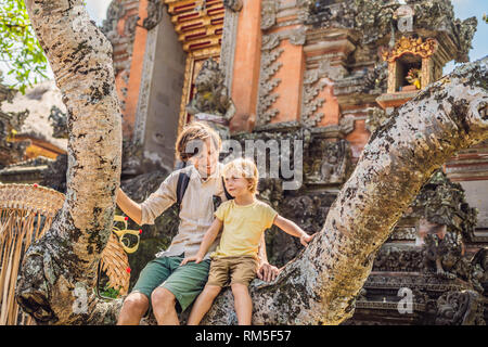 Dad and son travelers in the background of Pura Taman Kemuda Saraswati Temple in Ubud, Bali island, Indonesia BANNER, long format Traveling with - Stock Photo