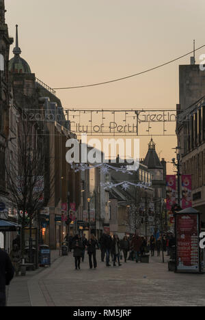 High street shoppers under Christmas lights at dusk in Perth, Scotland, UK - Stock Photo