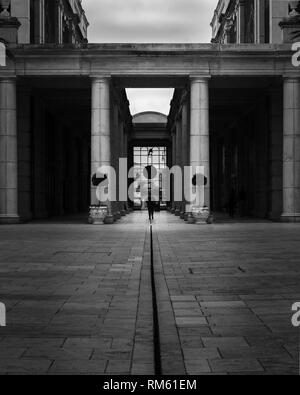 A man walks through an ostentatious tunnel surrounded by awesome architecture in black and white - Stock Photo