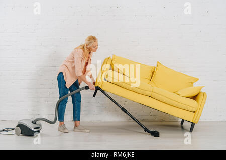 Full length view of senior woman with vacuum cleaner cleaning floor under yellow sofa - Stock Photo
