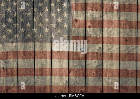 faded american flag painted on the side of an old weathered barn background - Stock Photo