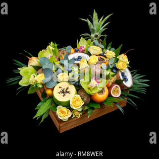 Wooden box with lots of exotic fruits and flowers isolated on black background as a gift - Stock Photo