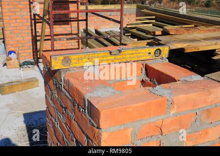 Building brick chimney on new house construction. - Stock Photo