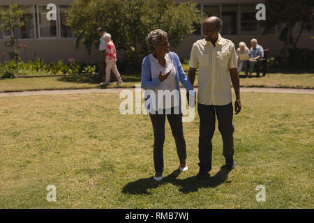 Front view of senior couple holding hands and interacting with each other in garden - Stock Photo