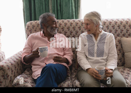 Senior couple interacting with each other while having coffee in living room - Stock Photo