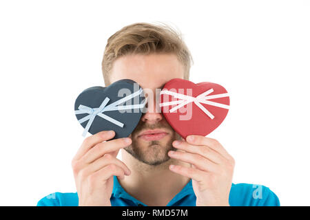 Guess which one. Man holds two heart shaped gift boxes in front of eyes, white background. Macho prepared romantic surprise for valentines day. Valentines day gift. Romantic surprise for her. - Stock Photo