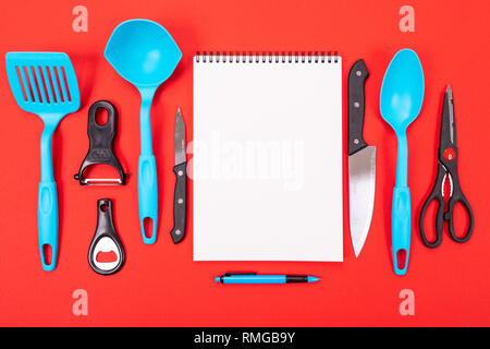 top view of a clean sheet and kitchen utensils next to it isolated on a red background - Stock Photo