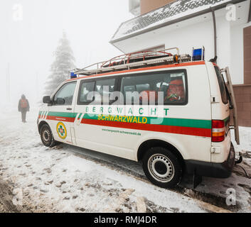 MUMMELSEE, GERMANY - JAN 26, 2019: Tourists woman near the Bergwacht Schwarzwald equipped van part of the German Red Cross (DRK-Bergwacht), whose primary functions are mountain rescue and nature conservation  - Stock Photo