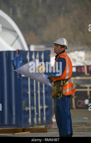 A builder consults his plans at the construction site - Stock Photo