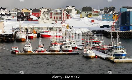 Quiet snowy Arctic village with fishing boats in the harbour, Norway - Stock Photo