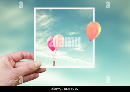 Hand holding an instant photo with air balloons, think outside the box concept - Stock Photo