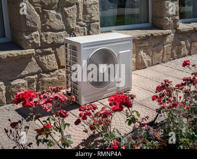 High efficiency modern AC-heater inverter unit, energy save solution-horizontal, outside a residential home - Stock Photo