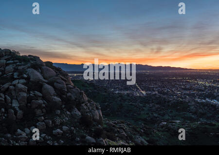 Dramatic dawn view of the San Fernando Valley neighborhoods from rocky hilltop in the city of Los Angeles, California. - Stock Photo