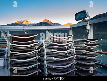 Stacked and secured lounge chairs on cruise ship outdoor deck with early morning sunrise light on mountainous background, near Skagway, Alaska, USA. - Stock Photo