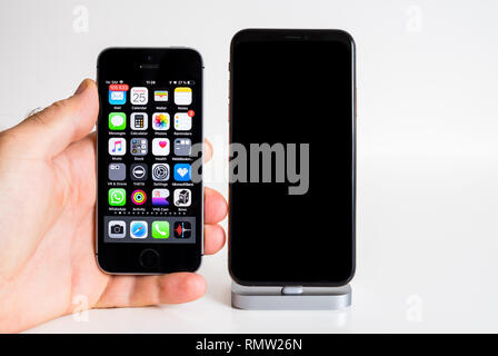 PARIS, FRANCE - SEP 25, 2018: Male hand compare new iPhone Xs and Xs Max smartphone model by Apple Computers close up with iphone SE - Stock Photo