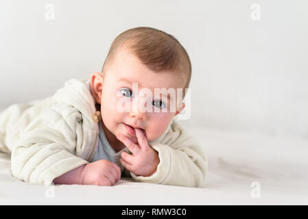 Portrait of an adorable smiling baby biting her own fingers putting her fist in her mouth. - Stock Photo