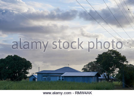 An Australian farm at dawn - typical rural architecture: weatherboard farmhouse, several sheds, a gazebo - all grey like the cloudy sky. Power-lines. - Stock Photo