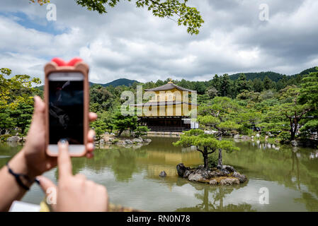 A tourist taking a picture of the Golden Pavilion, located in Kyoto, Japan, with a smartphone. The temple is traditionally known as Kinkaku-ji. - Stock Photo