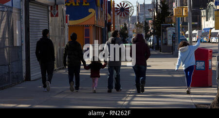 New York, USA. 16th February, 2019. A group of people walk side-by-side on Surf Avenue at Coney Island in Brooklyn, enjoying the day, a sunny winter Saturday afternoon in February, as the shadows of Luna Park's wooden Cyclone roller coaster (out of view on the left), listed on the New York State Register of Historic Places, fall upon them. Two of the people stroll on either side of a little girl with curly hair, each holding one of her hands. Another girl balances as she walks along the cracks in the sidewalk (pavement), an AM New York newspaper rack in front of her. Kay Howell/Alamy Live News - Stock Photo