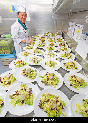 Salads being prepared in galley for Main Dining Room dinners on Holland America's cruise ship m/s Westerdam. - Stock Photo