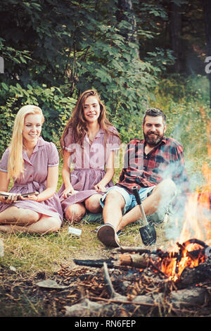 Smiling friends sitting next to campfire. Happy youngsters camping in forest. Bearded guy lying on grass while girls read books - Stock Photo