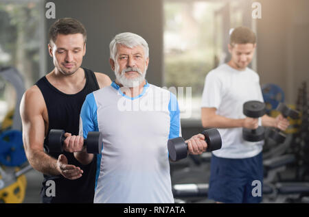 Professional fit trainer helping people in gym with doing exercises. Elderly man holding dumbbells in hands, looking at camera and posing. Man with gray hair wearing in sportswear. - Stock Photo