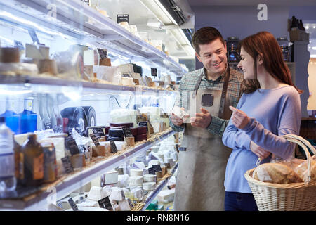 Male Sales Assistant Giving Advice To Female Customer In Delicatessen Shopping For Cheese - Stock Photo