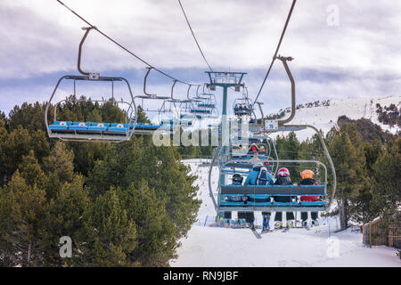 10 February 2019 - El Tarter, Andorra. Picture of skiers using chairlifts in the ski resort of El Tarter. Pinewood forest in the snowy mountains. - Stock Photo