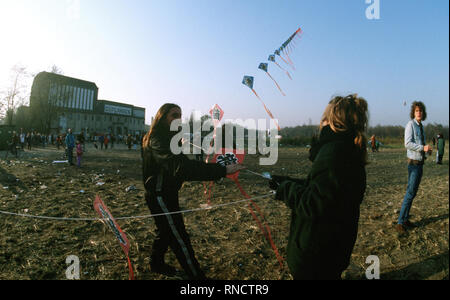 East Germans fly kites as they celebrate the demolition of a section of the Berlin wall at Potsdamer Platz. - Stock Photo