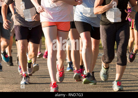 A pack of runners competing in a local five thousand meter race, both men and women together, on a sunny summer early evening - Stock Photo